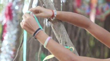 Dívka dekoratér vázací stuhy na větve