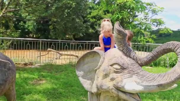 little girl sitting on elephant sculpture