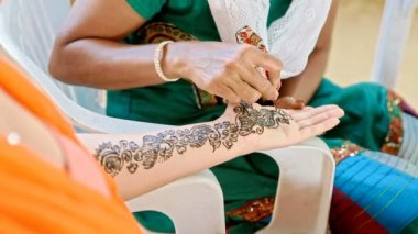 girl applies henna patterns on hands and arms of girl