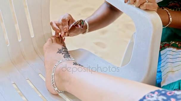 Indian woman draws tattoo on girl foot