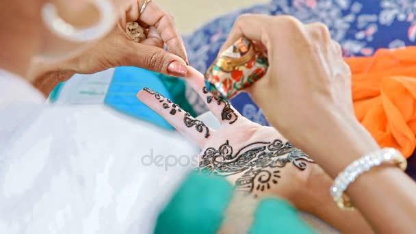 Indická dívka mistr nakreslí květinové vzory na prstech