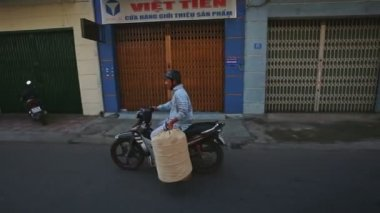 Man rides on motorbike and carries bag