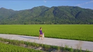 Woman with daughter walking down road among fields