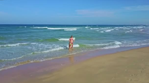 mommy and daughter walking and playing in ocean