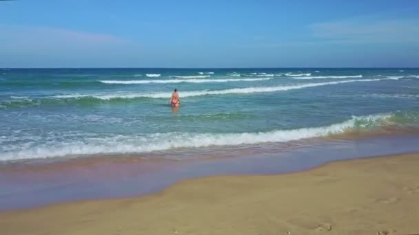 mother and daughter walking and playing in ocean