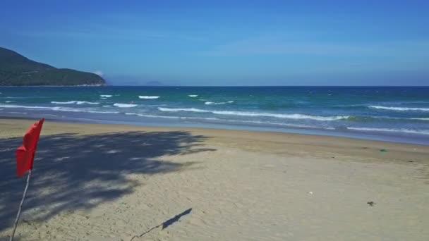 flag and tree shadow on ocean beach