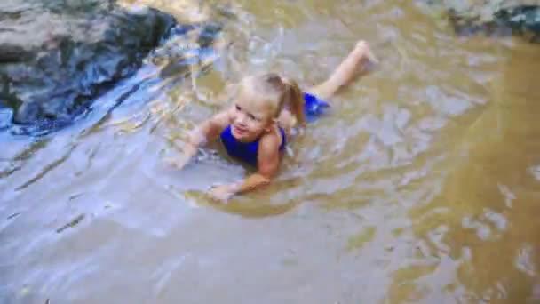 lány úszik, patak, vízesés között sziklák közelében