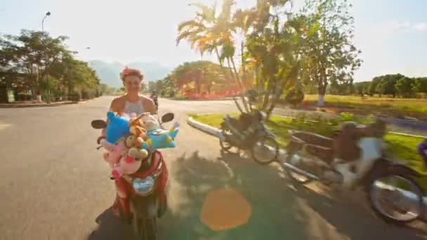 dívka rychlostí na mopedu s hračkami se podél silnice