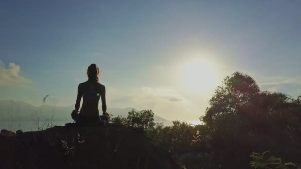 ragazza che fa yoga sulla grande scogliera