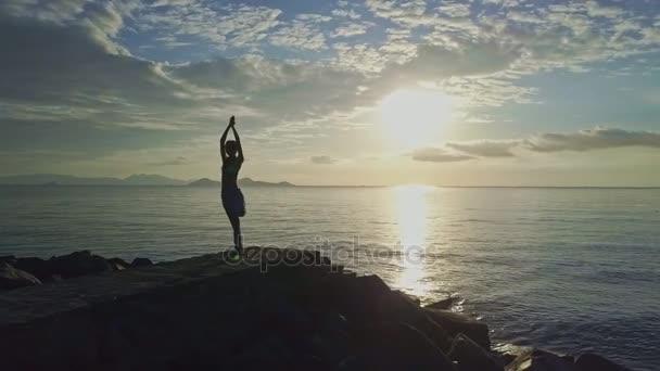 Mädchen macht Yoga am felsigen Strand
