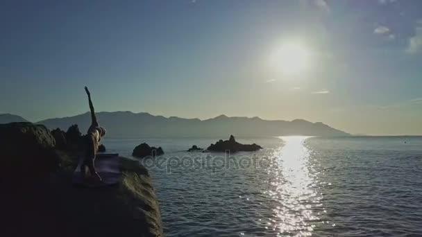 girl doing yoga on ocean coast