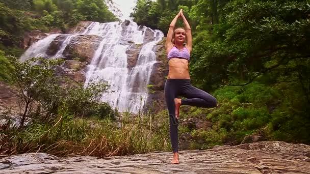 Žena, která dělá jógu poblíž vodopád