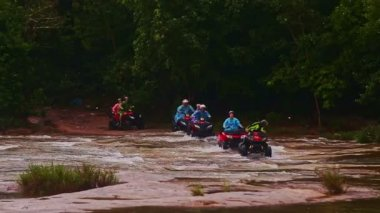 Tourists drive all terrain vehicles across river