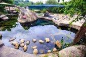Transparentní rybník mezi kamennou plošinu v parku