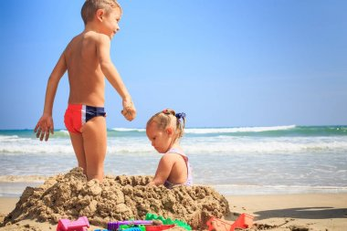 Girl and Boy Stands on Beach