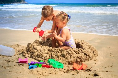 Girl and Boy Build Sand Castle on Beach