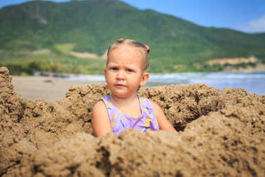 closeup little blonde girl sits in sand hole from mug on ocean beach against blue sea