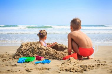 Girl and Boy Sit by Sand Heap on Beach