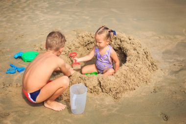 Girl and Boy Play on Beach