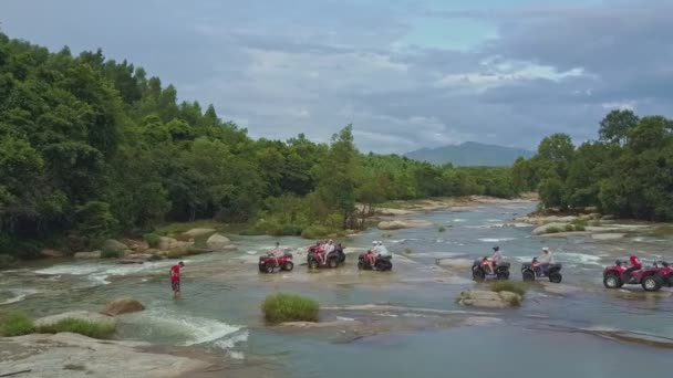 people drive quadricycles along powerful river