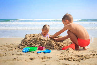 Girl and Boy Sits on Beach