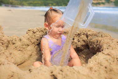 Girl Sits in Sand Hole behind Water on Beach