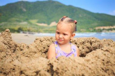 Girl Sits on Sand Beach
