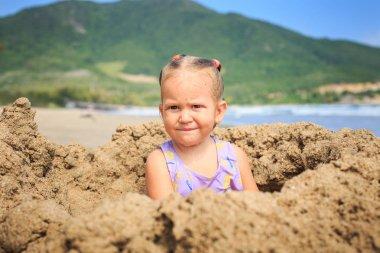 Girl Sits on Sand on Beach
