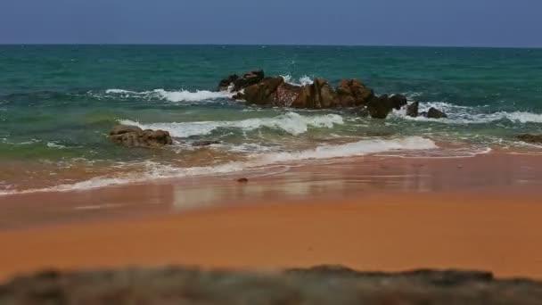 krásné tyrkysové oceánu a wave surf pády na skalách u písčité pláže, průzračně modré obloze