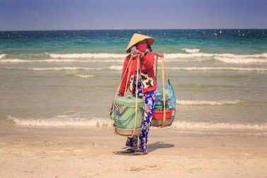 Closeup woman vendor in Vietnamese hat with baskets on yoke stands on ocean beach against azure sea and clear blue sky