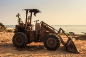 closeup small tractor with scoop stands on coast building ground against palms sea and blue sky