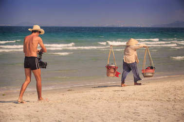 closeup European tanned young man in hat with camera follows local fruit vendor woman with vessels on yoke at beach