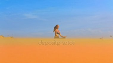 amazing view from below wind shakes blond long hair of young girl sitting in lotus pose on golden sand against blue sky