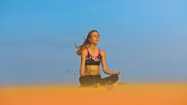 meditating yoga practitioner girl with waving by wind ponytail sits in pose lotus on beach sand