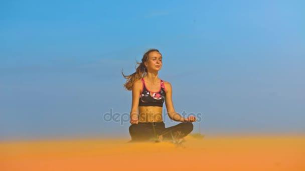 meditující jógy lékaře dívka s mává tím větrem ohonu sedí v pozici lotus na pláži písek