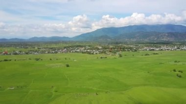amazing panorama wide green valley and village against mountains and sky with white clouds on horizon