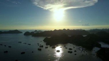 aerial amazing view tranquil bay with rocky islands silhouettes and boats against sunlight from behind cloud at sunset