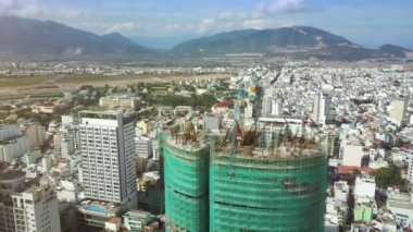 amazing upper view unfinished building covered with green mesh and broken cranes on top against far mountains