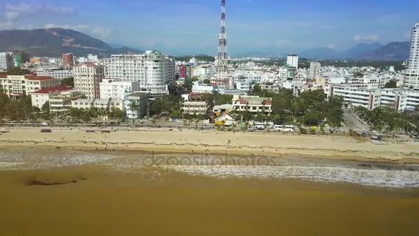 Panorama žluté moře vysoké vlny běžet na pláž a moderní město s mrakodrapy proti hoře a modré nebe nad hlavou