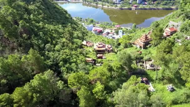 wonderful panoramic view ancient buddhist temple between green hills against modern city at bay coast
