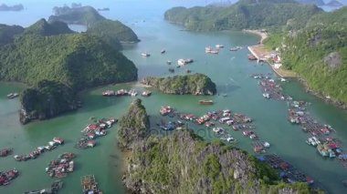 flycam moves over amazing tranquil ocean bay and floating village among rocky islands covered with jungles