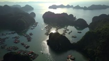 aerial view amazing calm ocean bay with floating village and boats among rocky islands and morning sunlight reflection