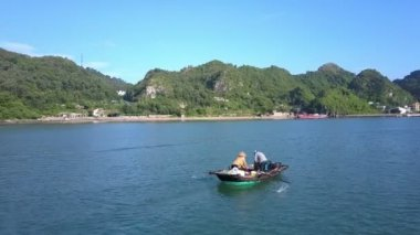 drone shows asian fishermen in wooden boat on ocean water and large mountain island covered with deep jungles