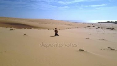 amazing panoramic view athletic woman sits among desert sand and blue clear sky in background
