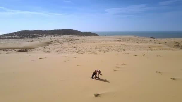 Skvělé horní panoramatický pohyb od azurové moře nízké zelené kopce a žena postava na písku v póze fitness