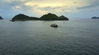 pictorial aerial view large tourist boat sails along amazing tranquil bay to hilly island beach with pier