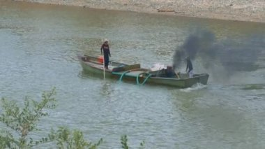 local people discharge sand with pipes out of river using small smoking engine and dredge sand to disposal site in boat