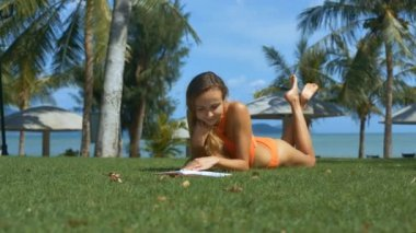 nice blond long haired girl in orange swimsuit lies on grass in park and reads paper book against beach umbrellas
