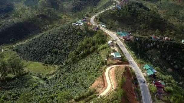 Letecký pohled na krásné moderní dálnice s jízdy auta a domy na silnici stranách na zelených kopcích