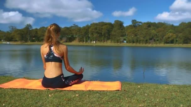 Closeup zadní pohled blonďatá dívka s culíkem sedí v Jóga pozici na břehu jezera a sleduje oblohu odrazem
